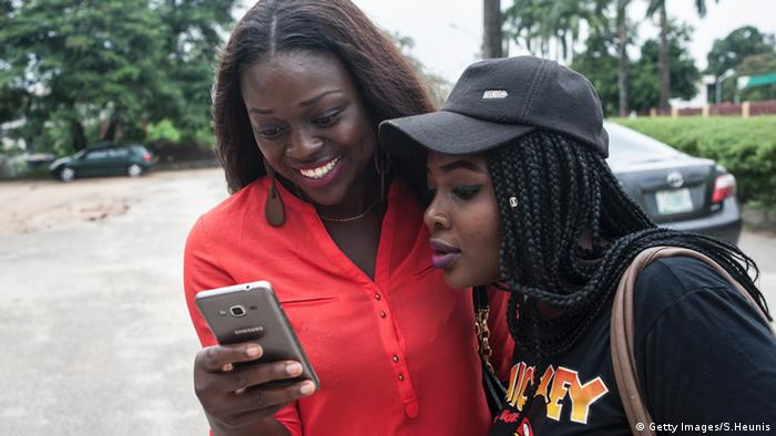 Two female students look at a mobile phone.