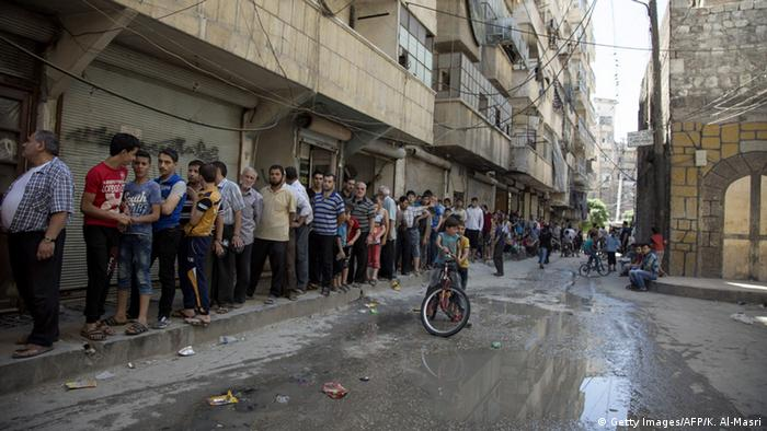 Aleppo residents queue to buy bread in a rebel-held neighborhood of Aleppo