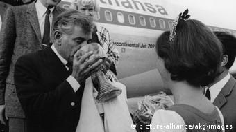 Leonard Bernstein given a big glass of white wine by Germany's Wine Queen