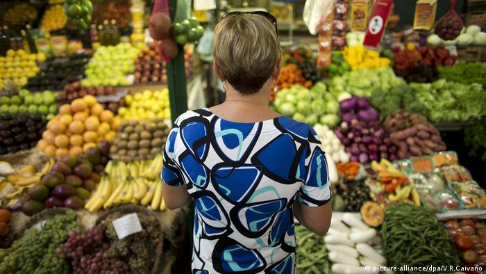 A woman looking at a fruit and vegetable stand