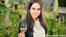 Ninorta Bahno aus Syrien posiert am 28.06.2016 in einem Weinberg in Trier (Rheinland-Pfalz) mit einem Glas Riesling-Wein. Die 25-jährige Christin, die vor dreieinhalb Jahren vor dem Krieg in ihrem Heimatland Syrien geflohen ist, wird Triers neue Weinkönigin. Gekürt wird sie am 3. August. Foto: Harald Tittel/dpa (zu lrs 0017 vom 29.06.2016) +++(c) dpa - Bildfunk+++ | Verwendung weltweit picture-alliance/dpa/H.Tittel