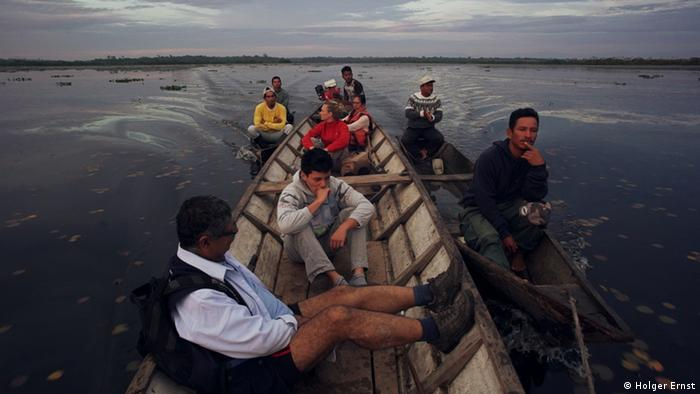 Reporter Carmen Meyer with fishermen and Peruvian project workers on a canoe.