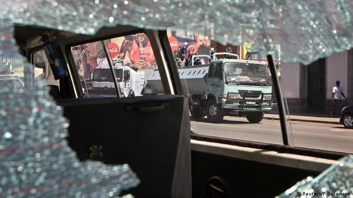 Riot police seen through a car's broken window