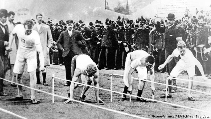 Foro histórica com espectadores e três atletas na largada dos 100m em 1896