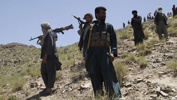 Taliban fighters stand guard as senior leader of a breakaway faction of the Taliban Mullah Abdul Manan Niazi, not pictured, delivers a speech to his fighters, in Shindand district of Herat province