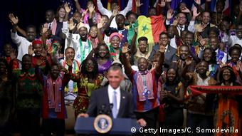 President Obama, behind him colorfully dressed youths from Africa.