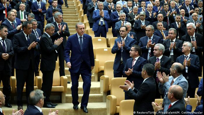 Erdogan descends steps inside presidential palace auditorium, as guests stand and applaud him.
