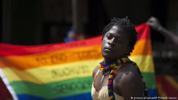 A transgender Ugandan demonstrating for gay rights in front of a rainbow flag