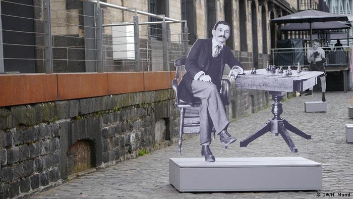 Ein Pappaufsteller von Lasker, der am Schachtisch sitzt steht im Freien auf einer Straße aus Kopfsteinpflaster. (DW/H. Mund)