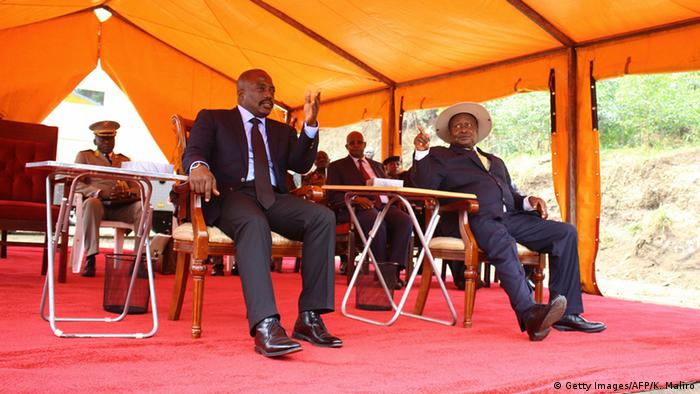 Ugandan President Yoveri Museveny (R) gestures as he sits under a marquee with DRC President Josef Kabila.