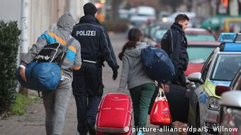 Three asylum seekers whose request has been denied walk away from the camera, accompanied by policemen.