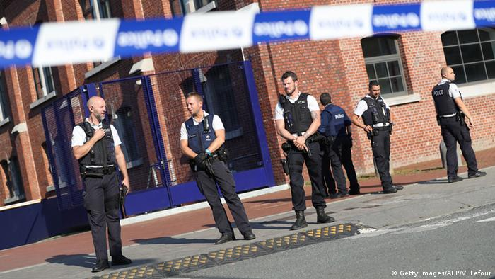 Police stand as they secure the area around a police building in the southern Belgian city of Charleroi