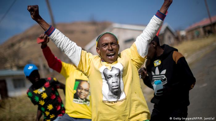 An ANC supporter in a yellow T-Shirt throws his hands into their air.