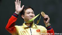 August 6, 2016*** epa05459509 Hoang Xuan Vinh of Vietnam celebrates with his gold medal on the podium after winning the men's 10m Air Pistol final of the Rio 2016 Olympic Games Shooting events at the Olympic Shooting Centre in Rio de Janeiro, Brazil, 06 August 2016. EPA/VALDRIN XHEMAJ +++(c) dpa - Bildfunk+++ | picture alliance/dpa/V. Xhemaj