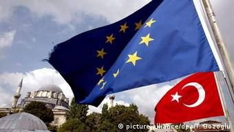 A tattered EU flag and a Turkish flag wave in front of the Hagia Sophia in Istanbul