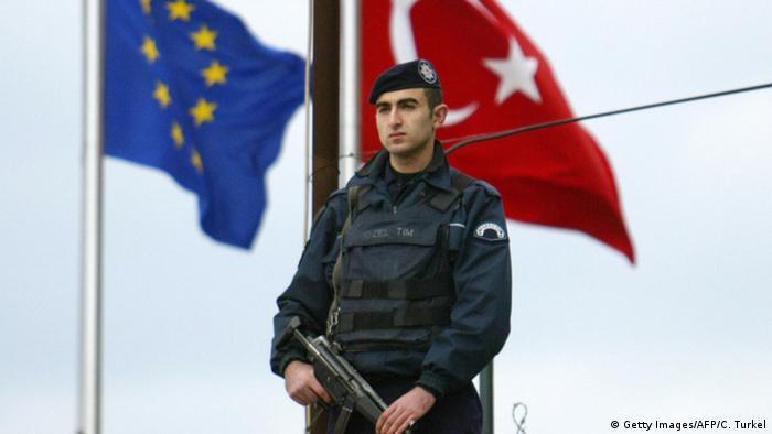 Турецкий полицейский на фоне флагов ЕС и Турции