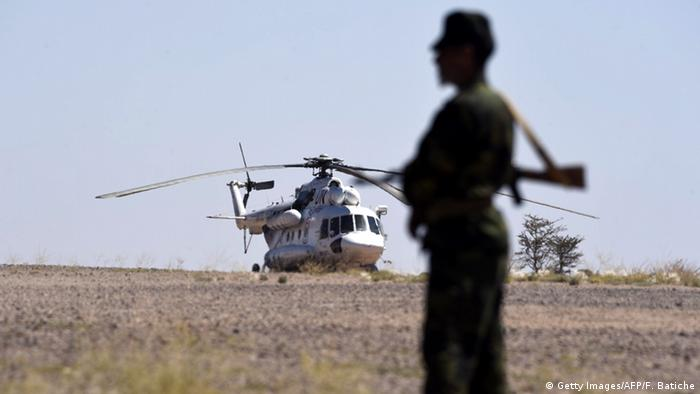 A UN helicopter sits on a field as a member of the Polisario Front stands guard during a visit by the Secretary General