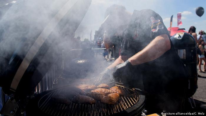 Runder Grill mit zahlreichen Fleischwaren, es steigt Dampf auf (Foto: picture-alliance/dpa/C. Welz).