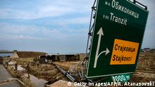7.08.2016 People stand near an overturned truck and a broken road sign by the ringroad close to the village of Stajkovci, near Skopje, on August 7, 2016. Fierce storms packing strong winds and torrential rains overnight killed at least 20 people in Macedonia's capital of Skopje, the health minister said August 7. The freak weather included winds blowing at more than 70 kilometres (43 miles) an hour and resulted in flash floods and landslides, with cars swept away by the violent torrents. / AFP / Robert ATANASOVSKI (Photo credit should read ROBERT ATANASOVSKI/AFP/Getty Images) Copyright: Getty Images/AFP/R. Atanasovski