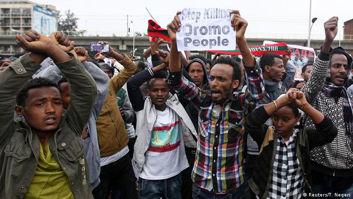 Demonstrators make the Oromo gesture, crossing their hands above their heads, during a protest in Addis Ababa