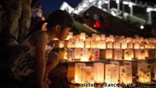 A young girl look at candle-lit paper lanterns with written message at Nagasaki Peace Park on the eve ahead of the 71st anniversary activities, commemorating the atomic bombing of Nagasaki on August 8, 2016 in Nagasaki, southern Japan. On August 9, 1945, during World War II, the United States dropped the second Atomic bomb, a plutonium implosion-type bomb on Nagasaki city, killing an estimated 40,000 people which ended the World War II. (Photo by Richard Atrero de Guzman/NurPhoto) | Keine Weitergabe an Wiederverkäufer. picture-alliance/dpa/A.Guzman