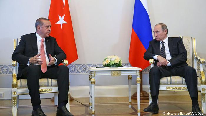 Sitting, Turkish President Recep Tayyip Erdogan talks with Russian President Vladimir Putin, with their respective flags behind them.