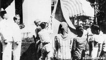 Ceremony of raising the flag of Indonesia moments after the reading of the Indonesian Declaration of Independence. The original flag was sewn by Sukarno's wife Fatmawati and flown every year on 17 August to commemorate the most important moments in Indonesian history. (Since 1968, a duplicate flag was flown to prevent the original from being damaged). Quelle: https://commons.wikimedia.org/wiki/File:Indonesian_flag_raised_17_August_1945.jpg#/media/File:Indonesian_flag_raised_17_August_1945.jpg Copyright: public domain
