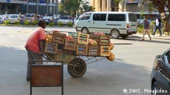 Straßenhändler schiebt Schubkarre mit Gemüse in Lusaka (Foto: DW/Chrispin Mwakideu)