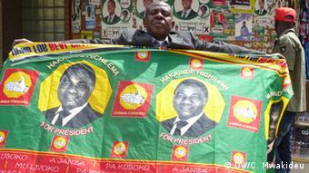 Nkole Mushula hält Stoffbanner mit Wahlwerbung für Hichilema (Foto: DW/Chrispin Mwakideu)