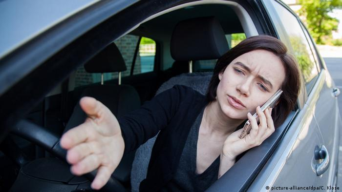 Woman speaking on her cell at the steering wheel (picture-alliance/dpa/C. Klose)