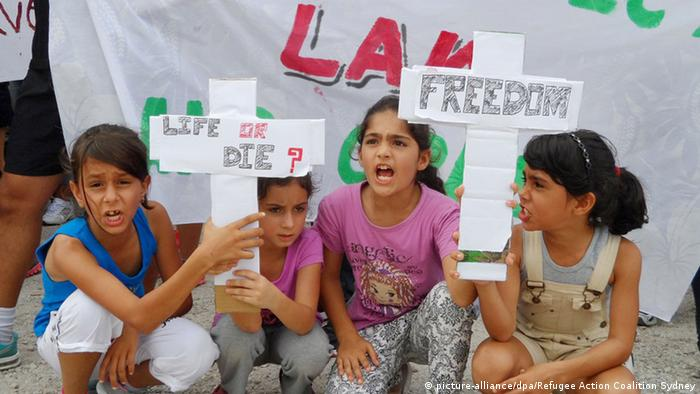 Four little girls hold up two cardboard crosses. One reads 'Life or Die' while the other says 'Freedom.'