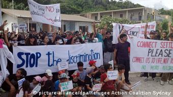 Protesters on the island of Nauru hold up signs, including the largest one which reads: Stop the discrimination