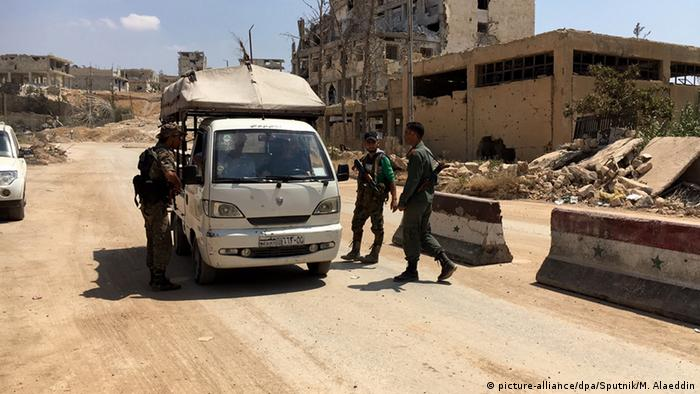 Three soldiers approach a small truck that has stopped at a checkpoint in Aleppo, Syria.
