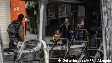 10.08.2016 People walk past security forces as they leave their houses during clashes in central Diyarbakir on March 15, 2016. / AFP / ILYAS AKENGIN (Photo credit should read ILYAS AKENGIN/AFP/Getty Images) Copyright: Getty Images/AFP/I. Akengin