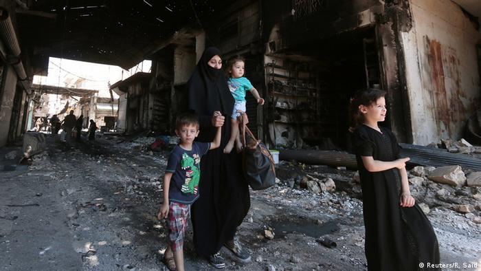 Syrien Manbij bei Aleppo Frau mit Kindern zwischen Trümmern