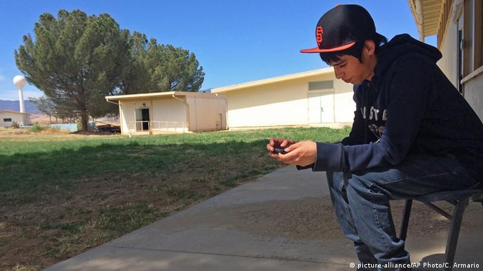 USA New Cuyama Junge mit Smartphone im Freien (picture-alliance/AP Photo/C. Armario)