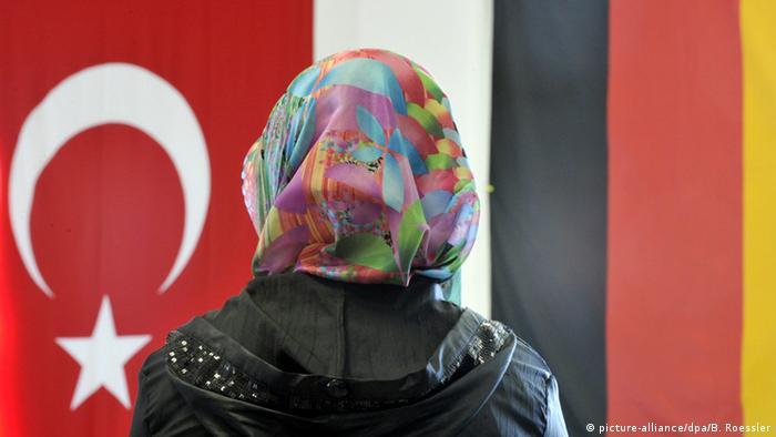 Deutschland Friedberg Frau mit Kopftuch vor türkischer und deutscher Fahne