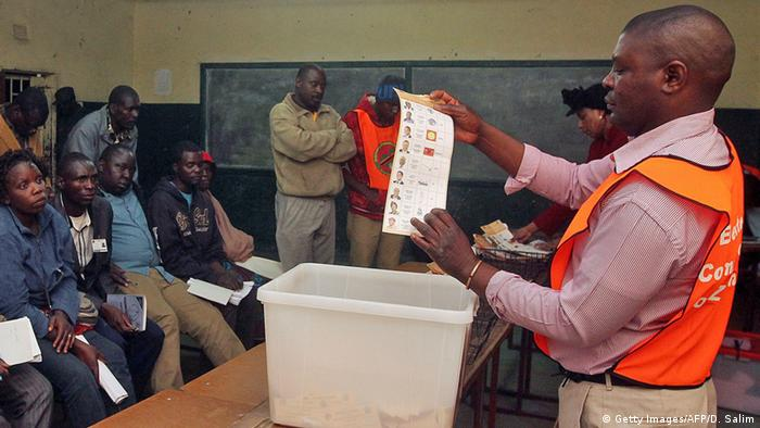 Zambian Electoral Commission officer holds a ballot paper during the vote counting process in a polling station