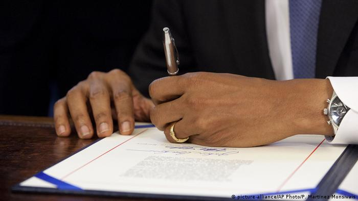 Barack Obama signing with his left hand