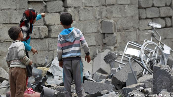 Yemeni children stand amidst the rubble of a house