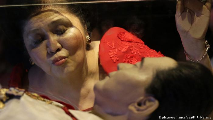 Imelda Marcos kisses the glass enclosure holding the preserved body of her late husband, Philippine president Ferdinand Marcos
