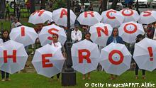 Protesters hold umbrellas with an anti-Marcos slogan during a demonstration at a park in Manila on August 14, 2016, against plans to honour the late dictator Ferdinand Marcos with a state burial (Photo: Getty Images/AFP/T. Aljibe)