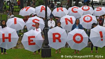 Protesters hold umbrellas with an anti-Marcos slogan during a demonstration at a park in Manila in August