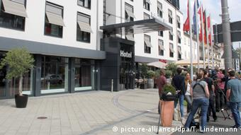 Journalists wait outside of a Kassel hotel where a closed-door AfD party meeting took place