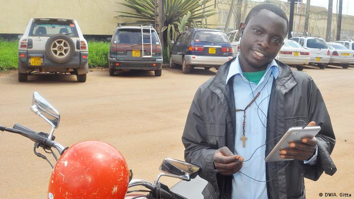 Motorbike taxi driver Mwanje Bernard holds a smartphone, standing in front of his motorcycle.