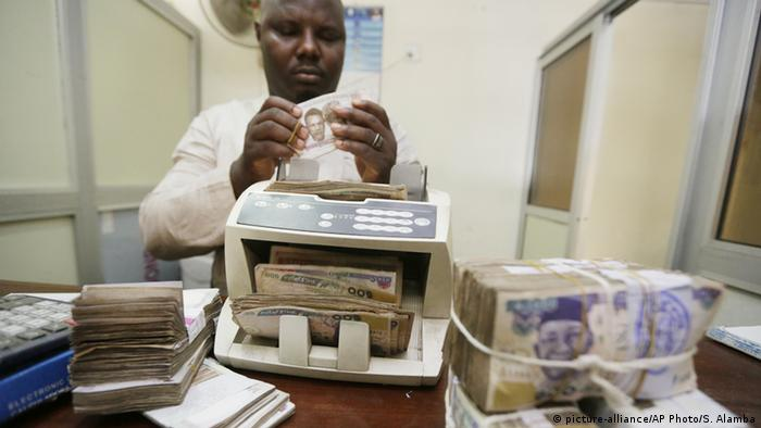 A Nigerian moneychanger puts Naira notes through a counting machine