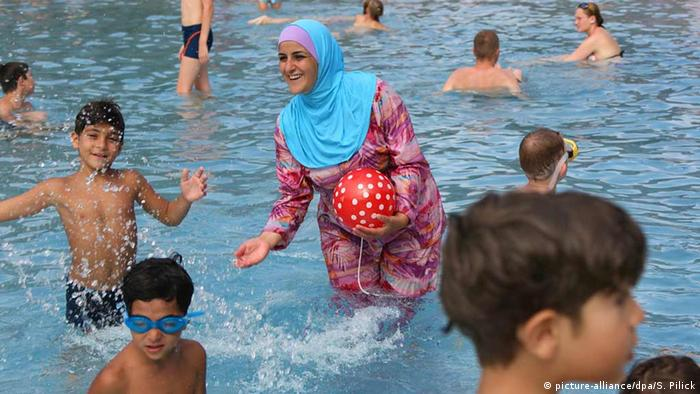 A woman wearing a burkini at a public pool (picture-alliance/dpa/S. Pilick)