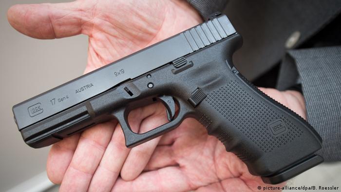 Пистолет, лежащий в открытой ладони