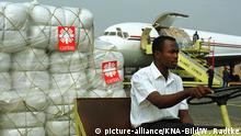 Caritas hilft nach dem Vulkanausbruch im Kongo beim Wiederaufbau Bild: Eine Frachtmaschine mit Hilfsgütern der Caritas wird auf dem Flugfeld in Kigsli / Ruanda entladen. Mit Lkws werden die Lebensmittel nach Goma transportiert. Copyright: picture-alliance/KNA-Bild/W. Radtke