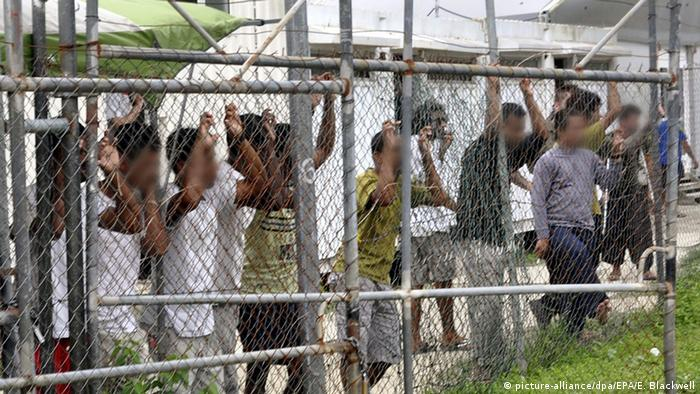 Men stand behind a fence at the Manus Island detention center